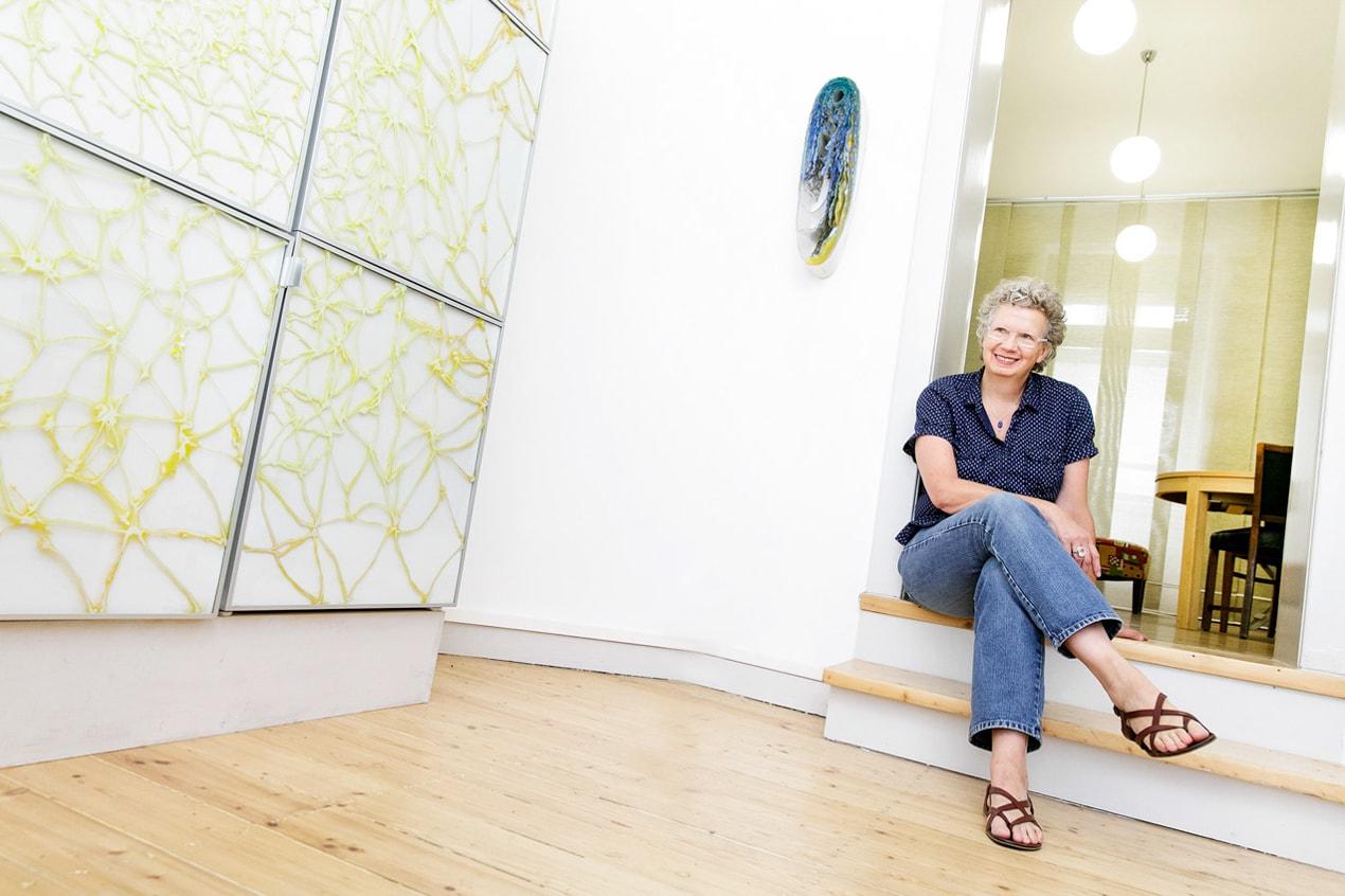 weitwinkliges Portrait von Elisabeth Ehrhorn auf der Treppe in ihrem Büro, Perserteppich, Raum, Schreiben- Pressefrauen Frankfurt schreiben und texten für PR