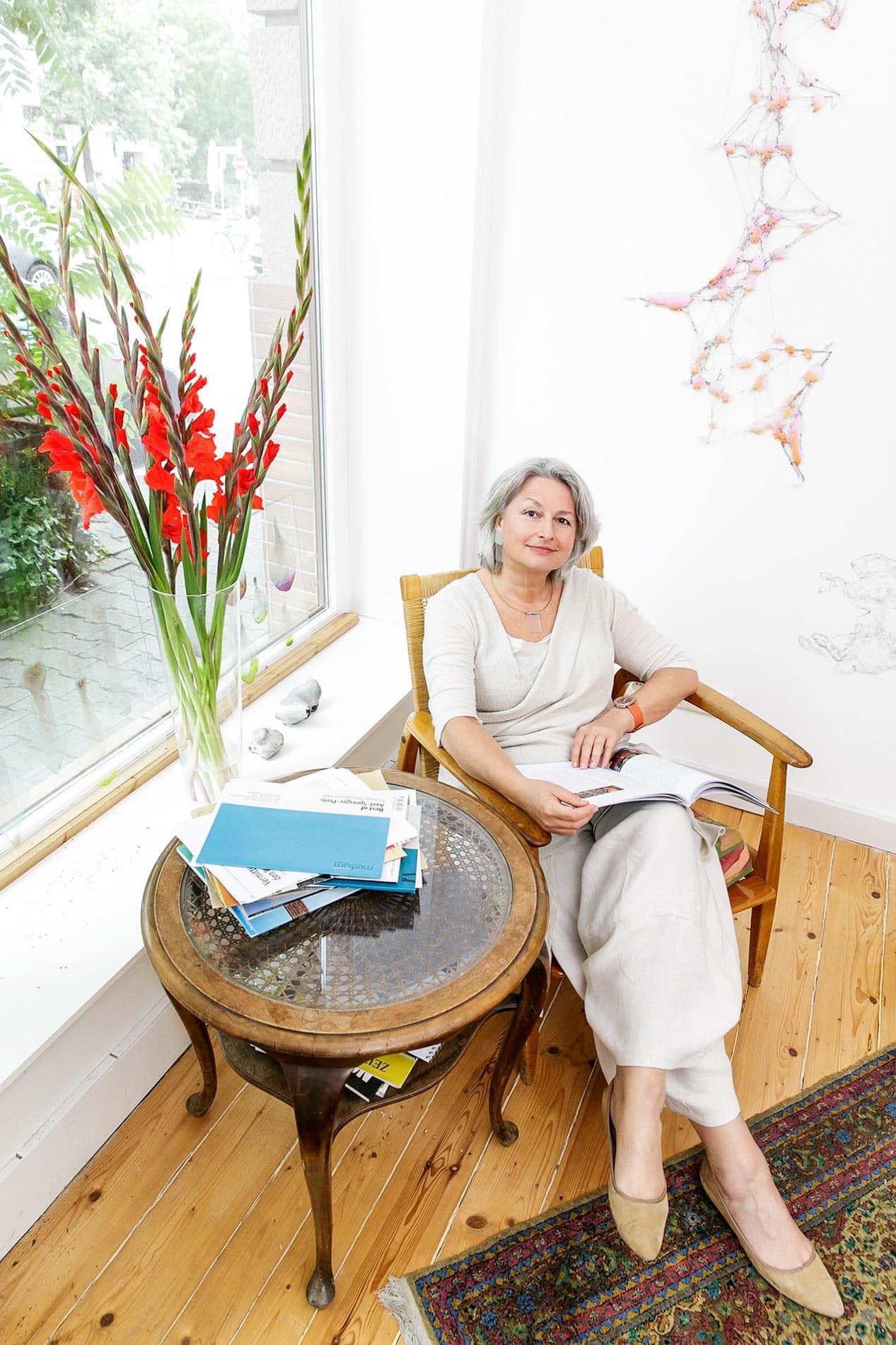 Portrait von Carmen Sorgler im Büro, sitzend am Tisch mit roten dekorativen Blumen im Fenster,Pressefrauen in Frankfurt