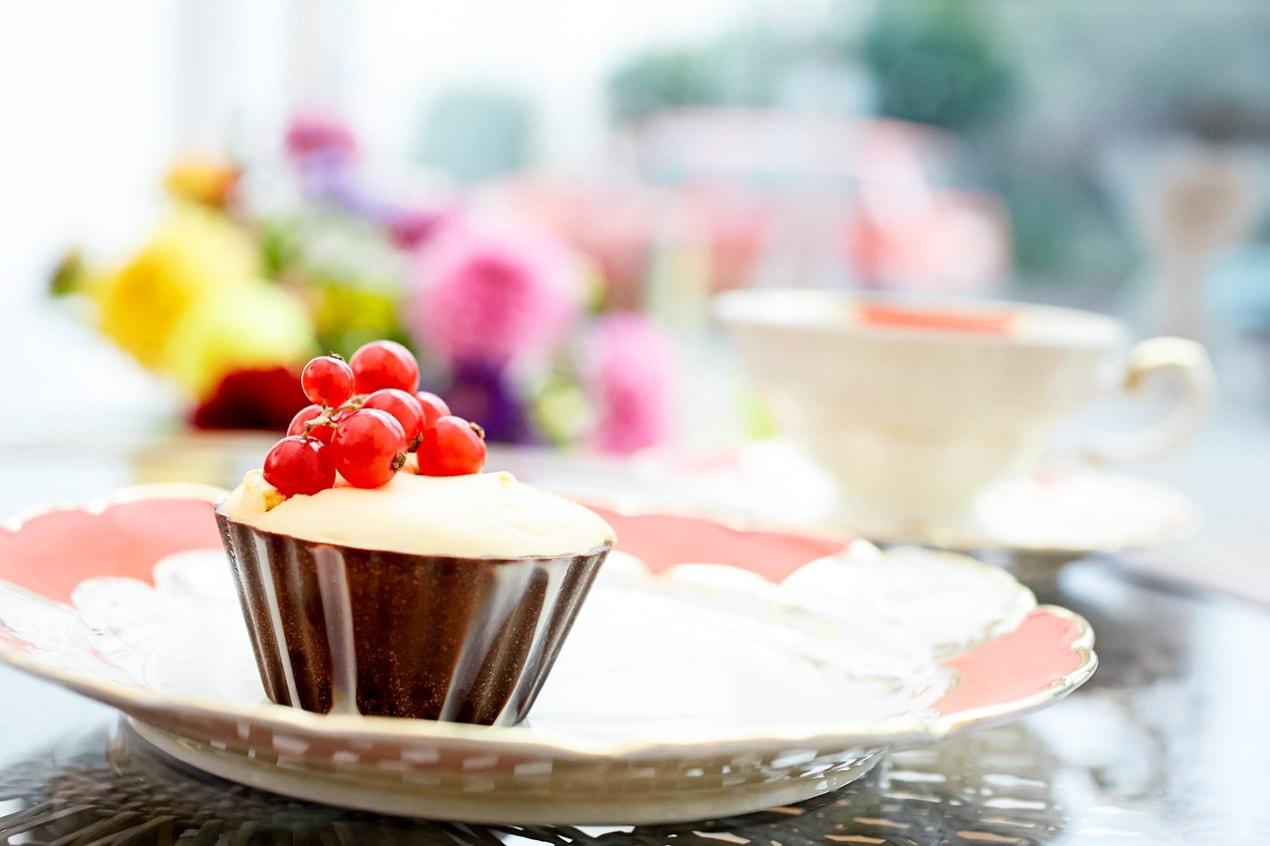leckerer Kuchen mit Johannisbeeren auf dekorativem Teller, orange weiß mit Blumen im Hintergrund- Pressefrauen Frankfurt schreiben und texten für PR