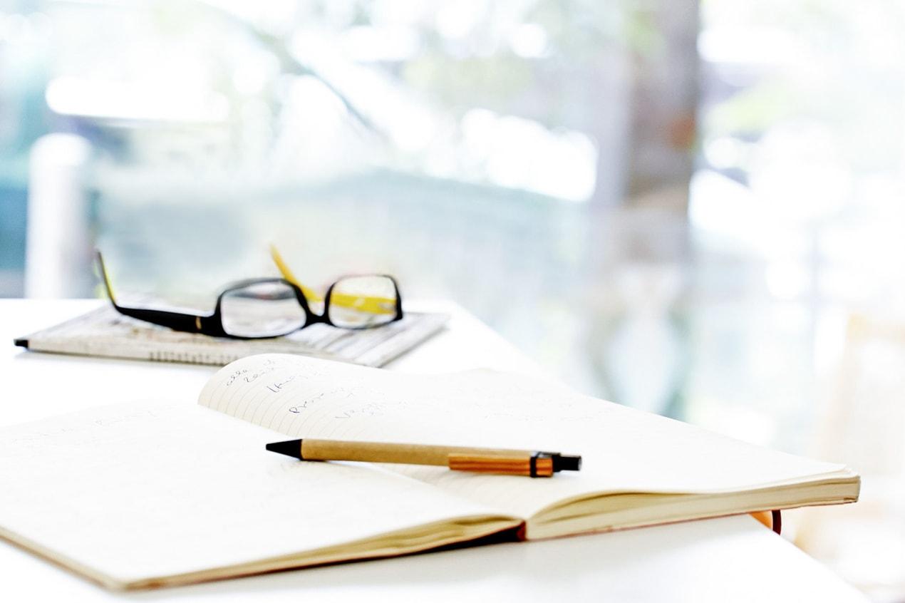 Detailaufnahme von Brille, Stift und Buch, Tisch,Raum, Büro, Schreiben- Pressefrauen Frankfurt schreiben und texten für PR