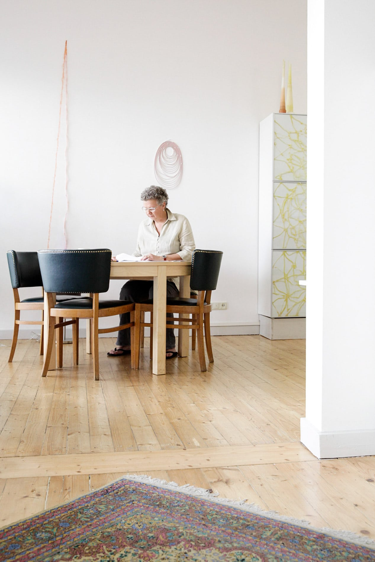 weitwinkliges Portrait von Elisabeth Ehrhorn sitzend am Tisch, Perserteppich, Raum, Büro, Schreiben- Pressefrauen Frankfurt schreiben und texten für PR
